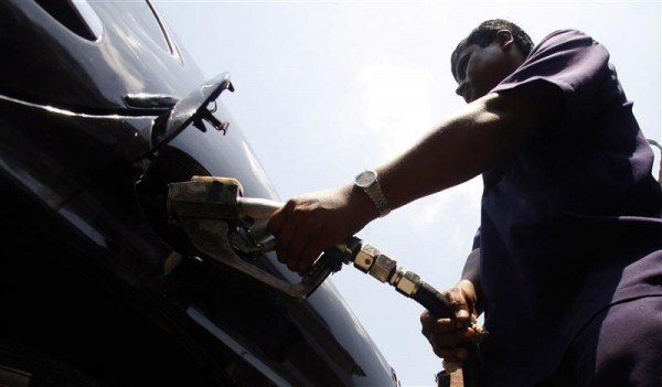 A petrol station employee pumps fuel into a car in Kolkata