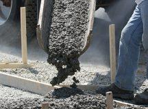 Construction worker pours concrete into sidewalk forms.
